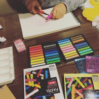 子どもがパステルを描いている写真